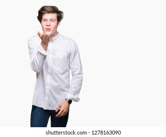 Young handsome business man over isolated background looking at the camera blowing a kiss with hand on air being lovely and sexy. Love expression.