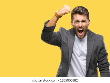 Young handsome business man over isolated background angry and mad raising fist frustrated and furious while shouting with anger. Rage and aggressive concept.