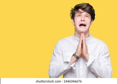 Young handsome business man over isolated background begging and praying with hands together with hope expression on face very emotional and worried. Asking for forgiveness. Religion concept.
