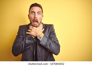Young handsome business man over yellow isolated background shouting and suffocate because painful strangle. Health problem. Asphyxiate and suicide concept.