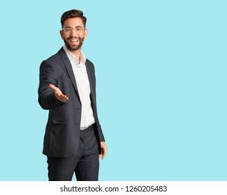 Young handsome business man reaching out to greet someone