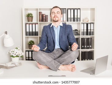 Young handsome business man relax in lotus pose in office