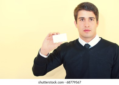 Young handsome business man showing a blank business card over uniform background