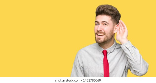 Young handsome business man smiling with hand over ear listening an hearing to rumor or gossip. Deafness concept.