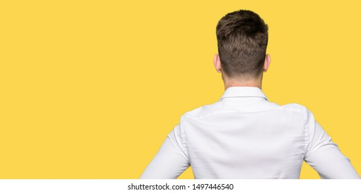 Young handsome business man standing backwards looking away with arms on body