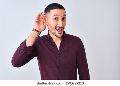 Young handsome business man standing over isolated background smiling with hand over ear listening an hearing to rumor or gossip. Deafness concept.