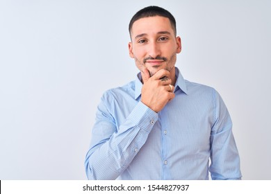 Young handsome business man standing over isolated background looking confident at the camera with smile with crossed arms and hand raised on chin. Thinking positive.