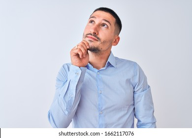Young handsome business man standing over isolated background with hand on chin thinking about question, pensive expression. Smiling with thoughtful face. Doubt concept.