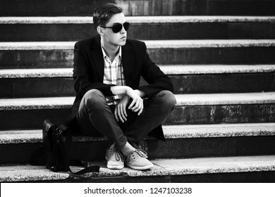 Young handsome business man in sunglasses sitting on steps Stylish male model wearing black jacket and gray pants