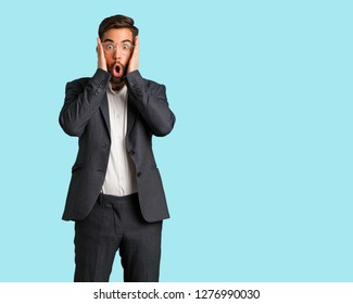 Young handsome business man surprised and shocked