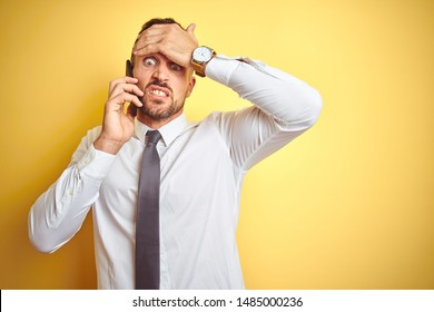 Young handsome business man talking on the phone over yellow isolated background stressed with hand on head, shocked with shame and surprise face, angry and frustrated. Fear and upset for mistake.