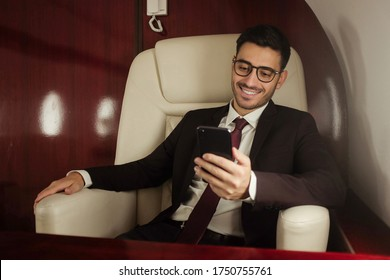 Young handsome business man travelling first class, sitting in armchair next to window, reading text messages on smartphone screen and smiling happily
