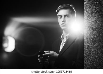 Young handsome business man using cell phone on city street at night Stylish fashion male model in black blazer