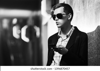 Young handsome business man using cell phone on city street Stylish fashion male model in black blazer and sunglasses