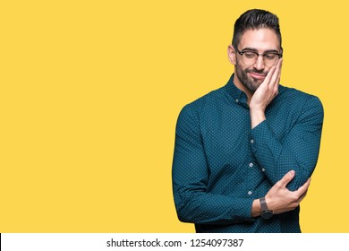 Young handsome business man wearing glasses over isolated background thinking looking tired and bored with depression problems with crossed arms.
