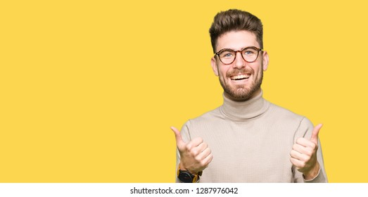 Young handsome business man wearing glasses success sign doing positive gesture with hand, thumbs up smiling and happy. Looking at the camera with cheerful expression, winner gesture.