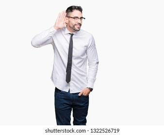 Young handsome business man wearing glasses over isolated background smiling with hand over ear listening an hearing to rumor or gossip. Deafness concept.