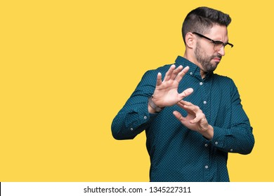 Young handsome business man wearing glasses over isolated background disgusted expression, displeased and fearful doing disgust face because aversion reaction. With hands raised. Annoying concept.