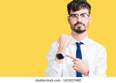 Young handsome business man wearing glasses over isolated background In hurry pointing to watch time, impatience, upset and angry for deadline delay