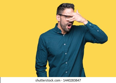 Young handsome business man wearing glasses over isolated background peeking in shock covering face and eyes with hand, looking through fingers with embarrassed expression.