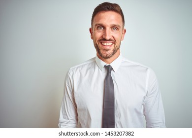 beb48b96 Young handsome business man wearing elegant white shirt over isolated  background with a happy and cool