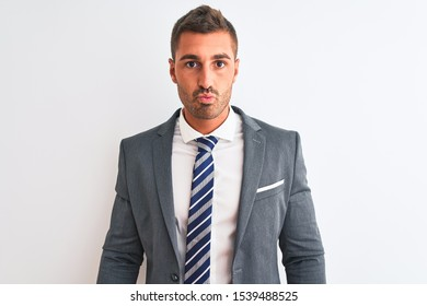 Young handsome business man wearing suit and tie over isolated background looking at the camera blowing a kiss on air being lovely and sexy. Love expression.
