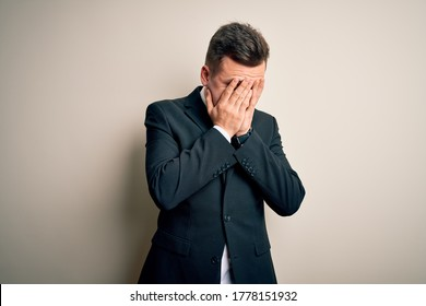 Young handsome business man wearing elegant suit and tie over isolated background with sad expression covering face with hands while crying. Depression concept.