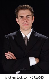 Young handsome business man wearing a suit and crossing his arms.