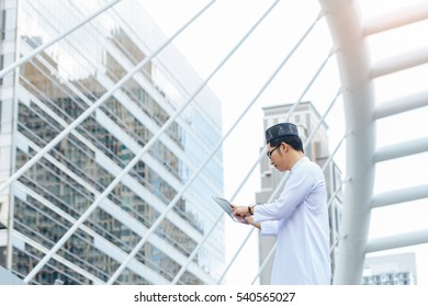 Young handsome businessman Arab Muslims looking at his business report in his tablet by internet network while standing at central of city. Business and technology concept.