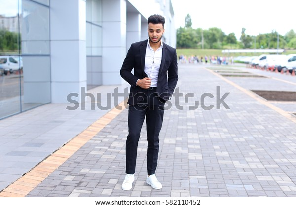 Young handsome businessman Arab Muslims is in the business center in black elegant dress on building background. Businessman man male looking at time walking goes and smiling.