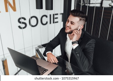 A young, handsome businessman in a black suit at the cafe called business dealers, he raises the handset with the help of wireless headphones, He laughs and discusses with them plans for the day