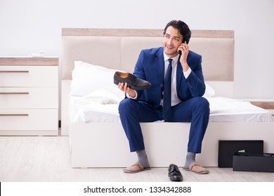 Young handsome businessman choosing shoes at home