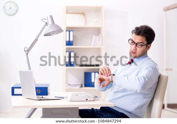 Young handsome businessman employee working in office at desk