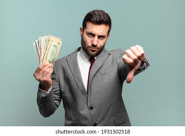 young handsome businessman feeling cross, angry, annoyed, disappointed or displeased, showing thumbs down with a serious look. bills or money concept