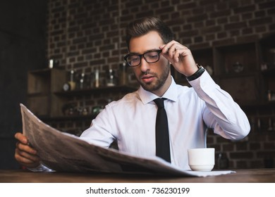 Young handsome businessman in formal wear and glasses, sitting at coffee shop and reading a newspaper