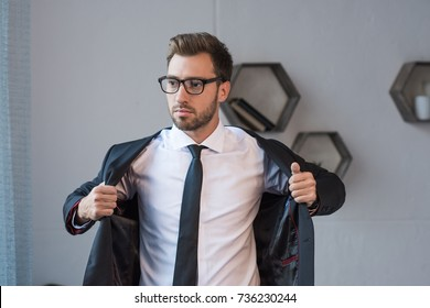Young handsome businessman in glasses putting on a formal blazer