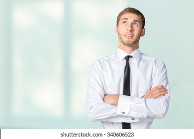 Young handsome Businessman with his arms crossed