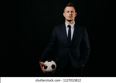 young handsome businessman holding a football on black background studio. blue jacket and tie. Stylish hairstyle model. World Championship.