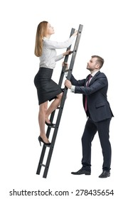 Young handsome businessman is holding a ladder for the lady in a formal clothes to boost her ideas. The concept of the success and team working