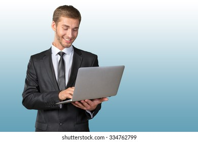 Young handsome businessman holding laptop