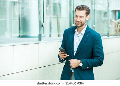 A young handsome businessman holding the phone and smile.