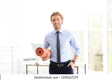 Young handsome businessman holding yoga mat in office. Gym after work