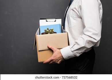 Young handsome businessman in light modern office with carton box. Upset office worker is fired.