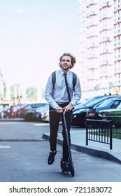 Young handsome businessman on street with kick scooter.