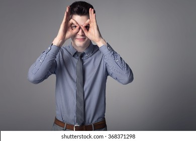 Young handsome businessman posing in studio, showing conceptual gesture, looking at camera. Elegant style.