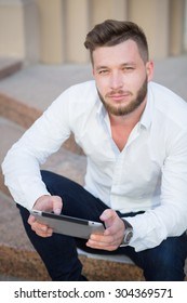 Young handsome businessman posing with tablet pc outdoors. Short-haired bearded man in white shirt looking so serious and demanding.