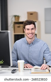 Young Handsome Businessman Sitting at his Worktable with Books, Computer and a Cup of Coffee While Smiling at the Camera