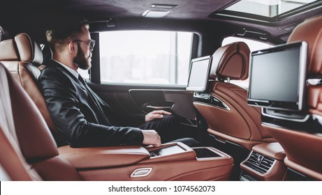 Young handsome businessman is sitting in luxury car. Serious bearded man in suit and glasses