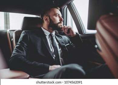 Young handsome businessman is sitting in luxury car. Serious bearded man in suit