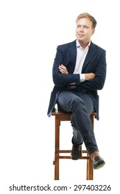 Young handsome businessman sitting on high wooden chair with crossed arms. He staring in the distance with slight smile. Confident and reliable person. Isolation white background